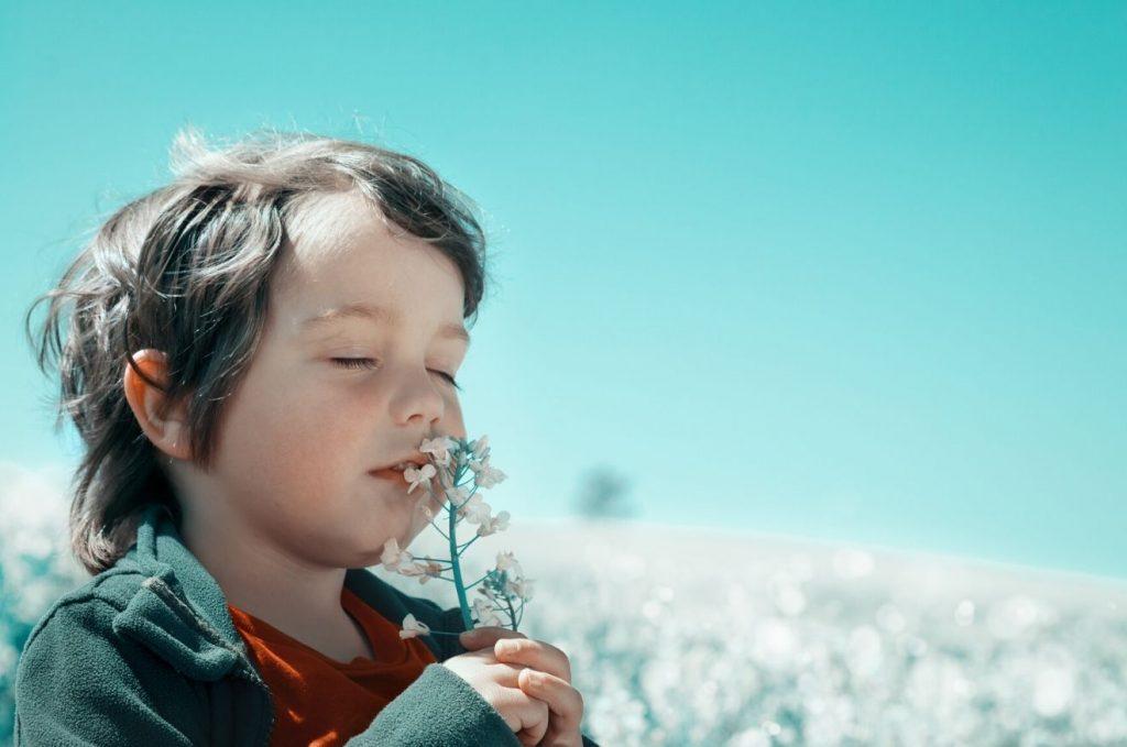 lapsi haistelee kukkia